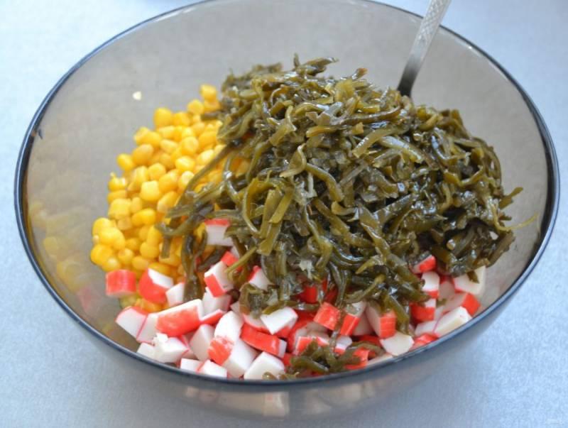 Мелко нарежьте крабовые палочки, добавьте их в салатник, добавьте туда же морскую капусту.