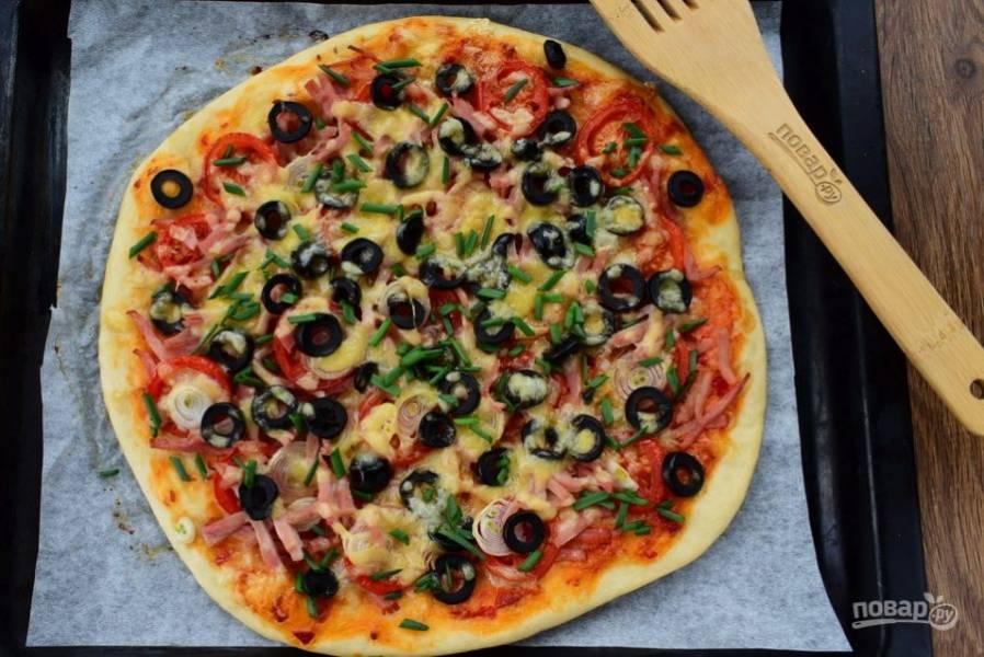Поставьте пиццу в разогретую духовку, выпекайте в течение 15-20 минут. Готовую пиццу присыпьте мелко нарезанным зеленым луком или зеленью.