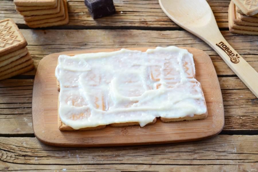 На блюдо или поднос выложите печенье по 3 шт. в два ряда. Я решила сделать небольшой тортик, а вы можете выбирать любой размер. Смажьте первый слой кремом.