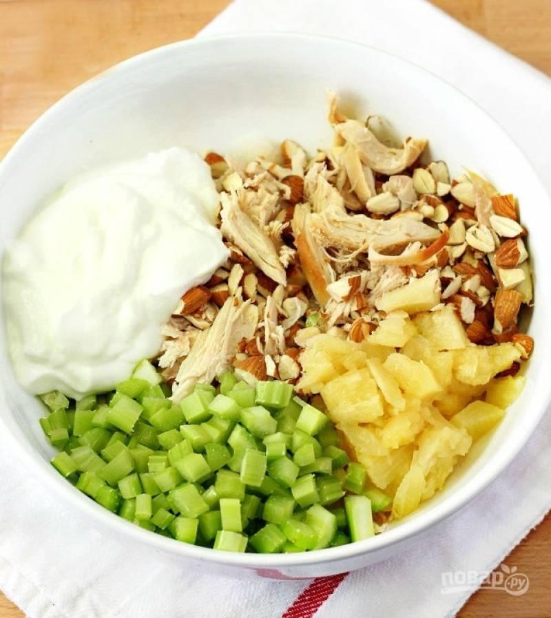 2.В салатник выкладываю курицу, ананасы, сельдерей, измельченный миндаль и добавляю нежирный натуральный йогурт (греческий), а также добавляю ананасовый сок, по вкусу солю.