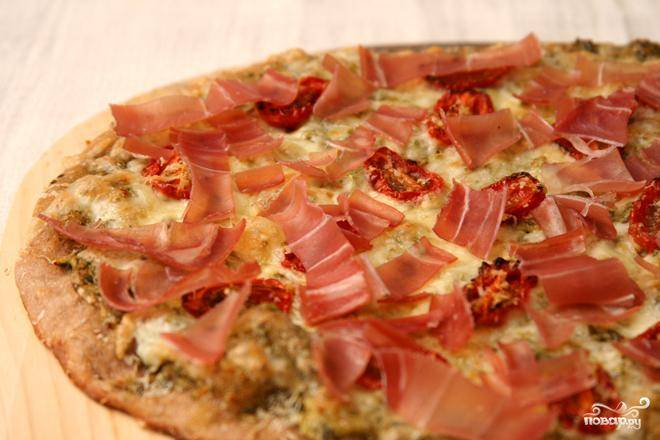 4. Выложить пиццу для охлаждения на решетку без пергамента. Посыпать нарезанной ветчиной прошутто. Дать пицце постоять 5 минут перед подачей на стол.