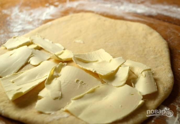 Раскатайте тесто в пласт, толщиной около 1 сантиметра. Затем визуально разделите пласт на две части и выложите на одну из них нарезанный пластинками холодный маргарин.