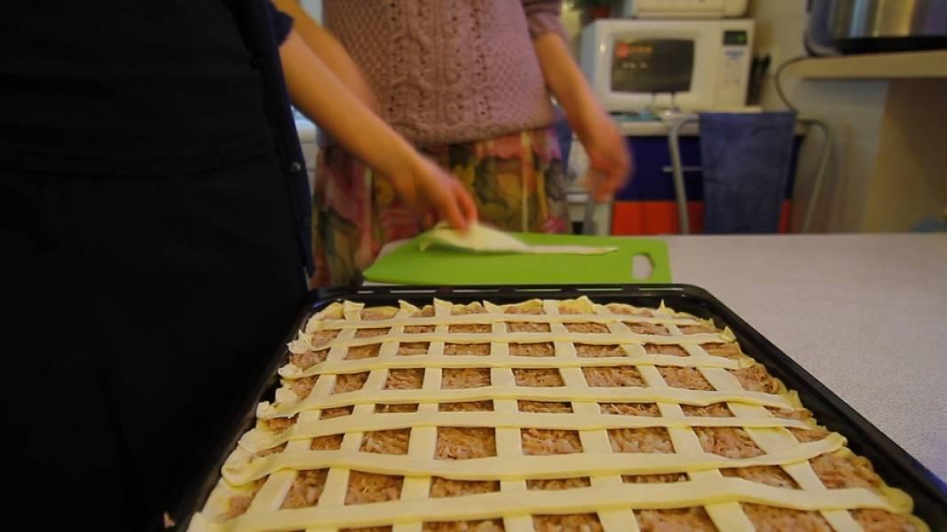Оставшуюся часть теста нарезаем на полоски и сеточкой выкладываем на начинку.