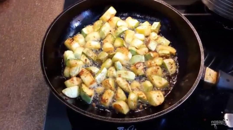 1. Для начала нарежьте кубиками кабачок, не солите его. Обжарьте кабачки на разогретом на большом огне оливковом масле, периодически помешивая.
