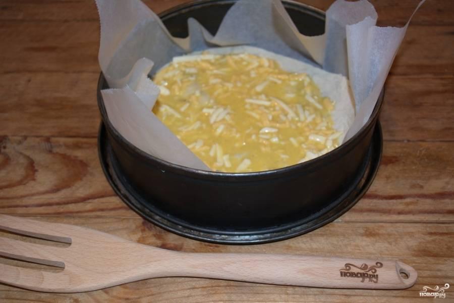 Форму застелите пекарской бумагой. На лист бумаги кладем лист лаваша, обрезанный по форме. На него — 2-3 столовые ложки смеси из сыра и яиц.