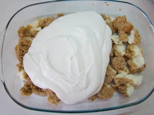 7. Выложите на дно формы половину кусочков бисквита и треть крема. Затем повторите слои.