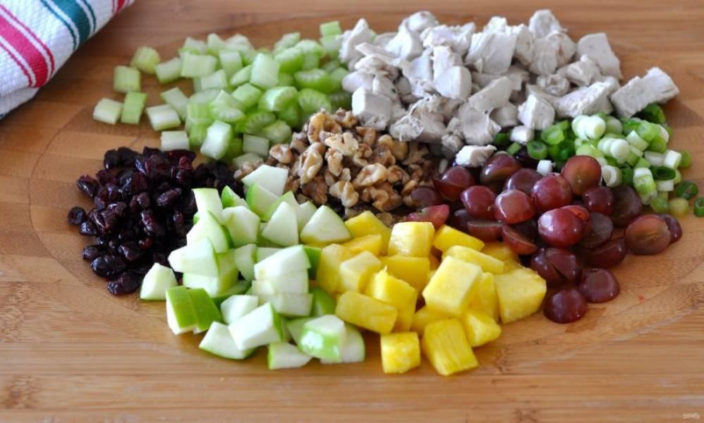Теперь моем все овощи и фрукты. Ананас чистим и режем кубиком, так же режем остывшее мясо и яблоко. Измельчаем сельдерей, зеленый лук и сушеную клюкву. Грецкие орехи рубим ножом, ягоды винограда режем на несколько кусочков.