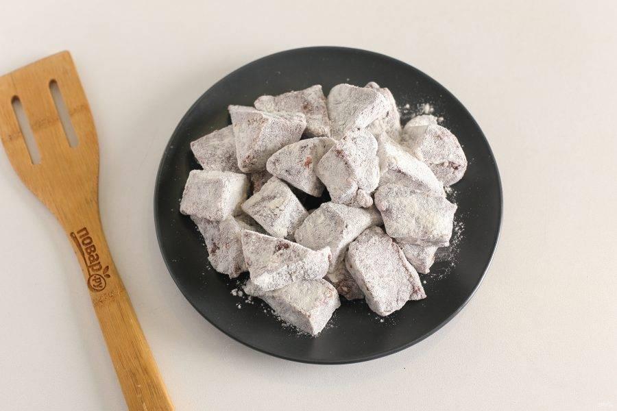 Печень нарежьте порционными кусочками и обваляйте в муке.