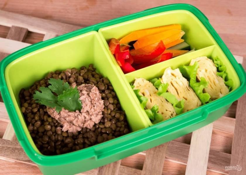4. Далее выложите омлет на дощечку и разрежьте на ровные части. Поместите омлет и отваренную чечевицу в ланч-бокс. К чечевице добавьте немного тунца. В отдельный отсек поместите овощи. Приятного аппетита!