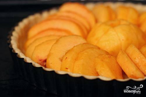 2. Разрезать персики пополам и удалить косточки. Нарезать тонкими ломтиками. Выложить персики поверх корочки для тарта, чтобы ломтики перекрывали друг друга. Взбить сливки, яйцо, сахар и миндальный экстракт вместе в небольшой миске. Залить полученную смесь поверх персиков. Выпекать тарт в течение 10 минут.