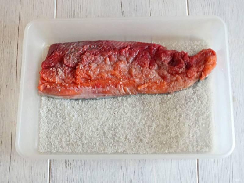 Возьмите лоток по размеру рыбы. На дно насыпьте 1/3 часть посолочной смеси. Выложите рыбу, сверху присыпьте солью с перцем и сахаром.