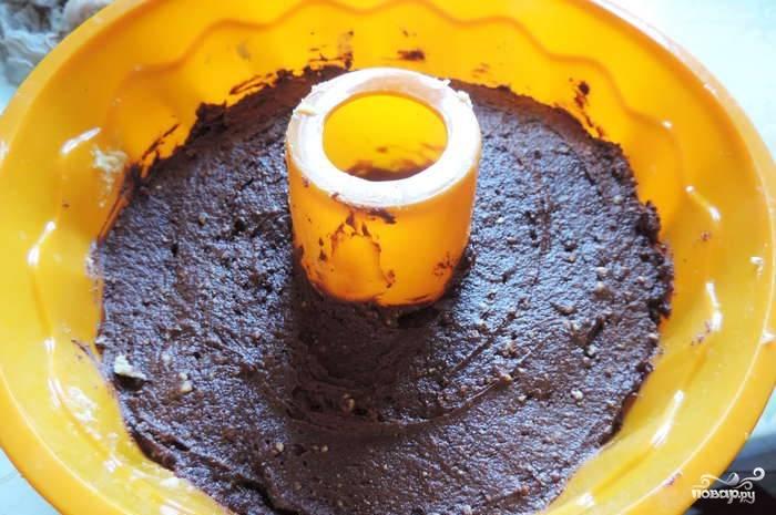Во вторую часть вливаем ароматизатор и насыпаем какао. Кладем разрыхлитель и стакан муки. Выкладываем шоколадный слой на первый слой с сухофруктами.