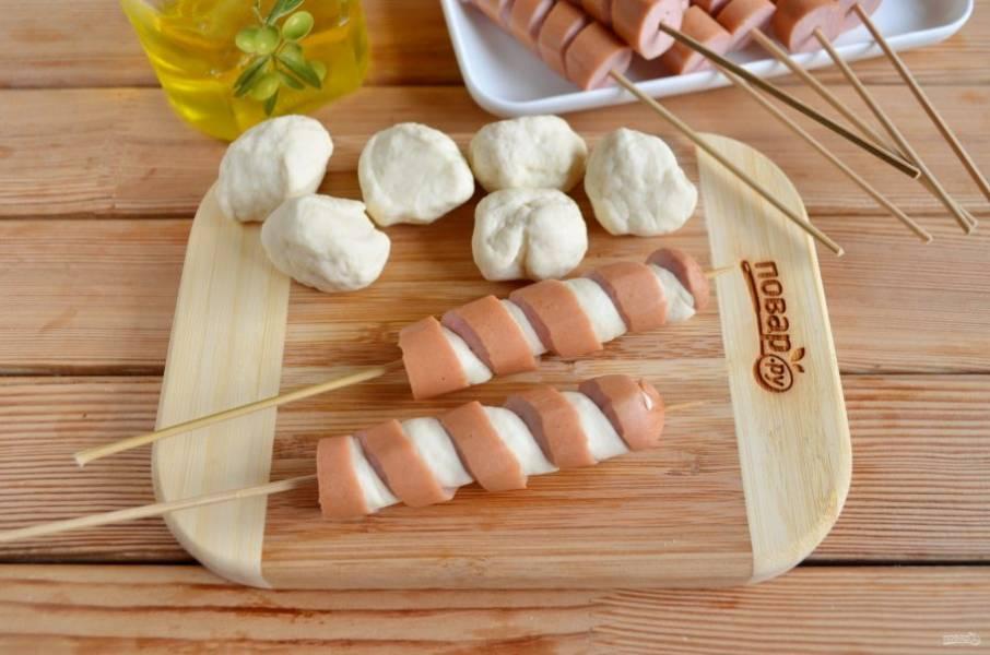 Вложите плотно жгутики между витками сосиски.