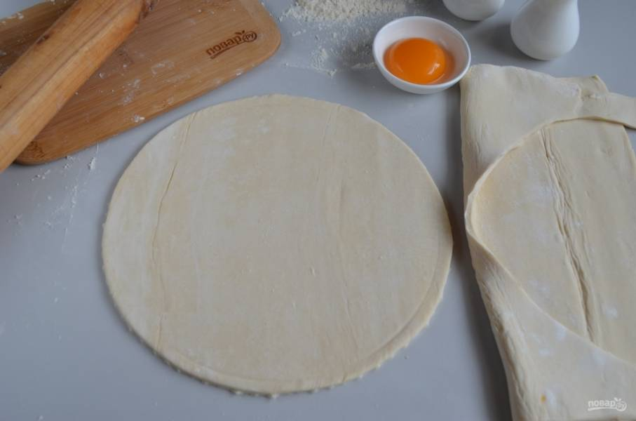 Разложите тесто на столе, осторожно ножом вырежьте круг по диаметру формы так, чтобы получились небольшие бортики.
