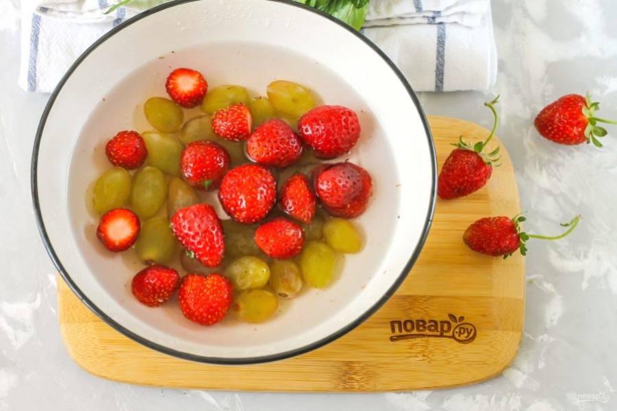Оборвите хвостики с ягод клубники. Виноградины снимите с кисти в глубокую емкость. Туда же добавьте очищенную клубнику и залейте холодной водой. Тщательно промойте несколько раз. Вместо клубники можно использовать любые сладкие ягоды: ежевику, малину, черешню, но не смородину и не вишню!