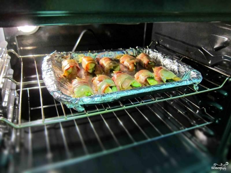 Поместите противень с рулетами в разогретую духовку и выпекайте в течение 12 минут при температуре 400 градусов. Поверните противень другой стороной, смажьте рулеты соусом и поставьте обратно в духовку на 12 минут.