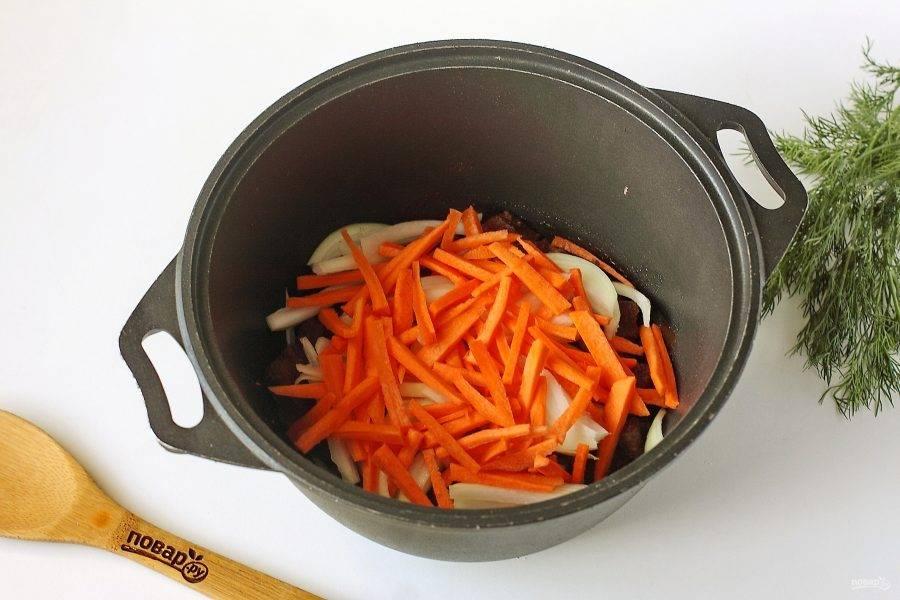 Добавьте к мясу нарезанную соломкой морковь и нарезанный перьями лук.