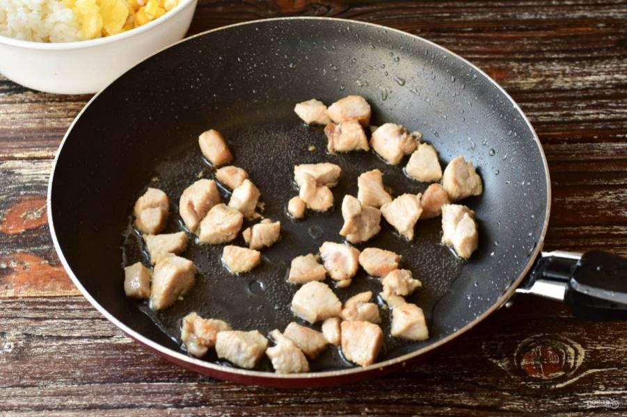 В сковороде разогрейте растительное масло. Выложите куриное филе, которое нарежьте средними по размеру кусочками. Обжарьте мясо в течение 5-7 минут.