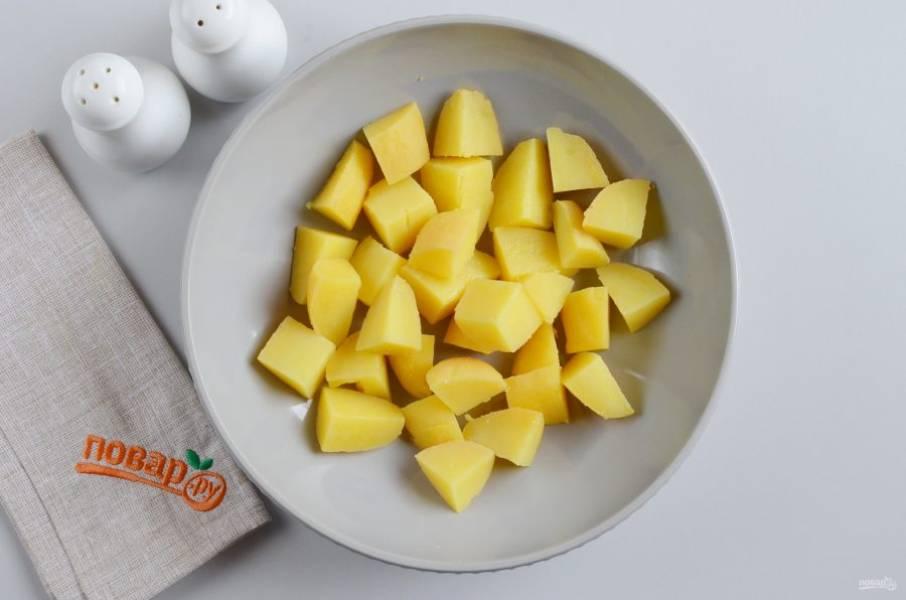 Картофель очистите от кожуры, порежьте небольшими кусочками, примерно на 1 укус. Выложите в большой салатник.