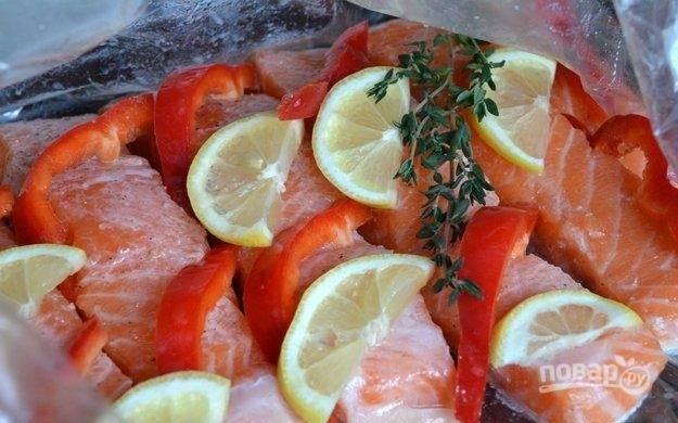 2.Мою болгарский перец, очищаю его от семян и нарезаю полукольцами, оставшуюся половинку лимона нарезаю тонкими дольками. В пакет для запекания аккуратно укладываю филе, на каждый кусочек сверху кладу полукольца перца и дольки лимона, добавляю веточку тимьяна и душистый перец.