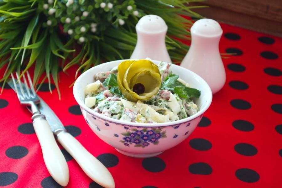 Соедините колбасу, соленые огурцы, все виды зелени, яйца в миске. Заправьте сметаной или майонезом. Не солите. Колбаса и огурцы имеют свою соль и салат и так достаточно соленый. Перемешайте. Подайте к столу.