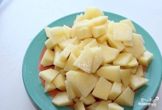 2. Помойте и очистите картофель. Нарежьте его кубиками. Положите в бульон, предварительно достав из него ребрышки.