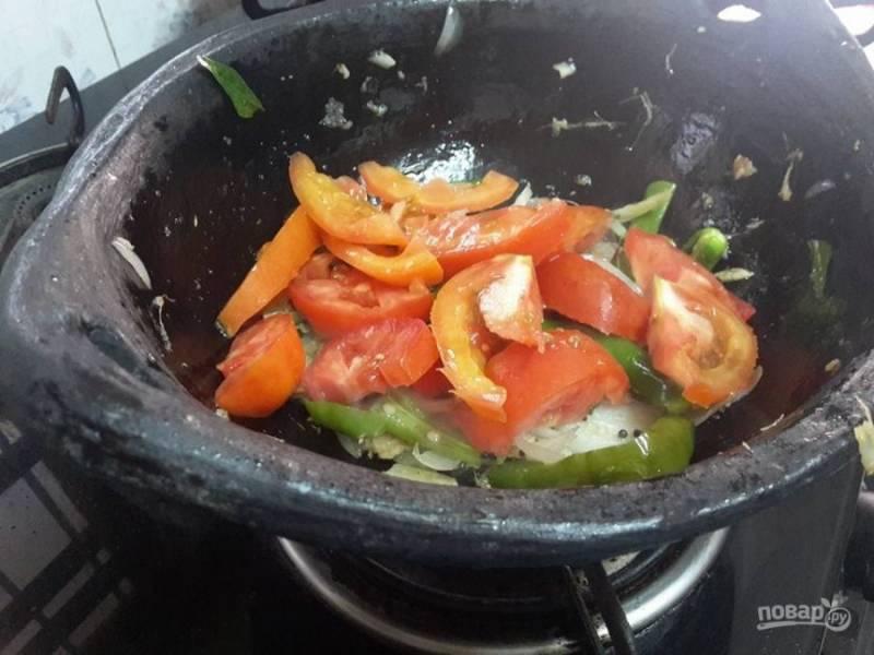 3. В отдельной емкости смешайте семена горчицы, кардамон, гвоздику и корицу. Затем добавьте измельченный лук, помидоры, имбирь, чеснок, чили и листья карри. Тушите овощи в течение 5 минут на среднем огне.