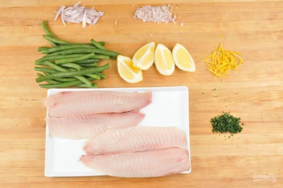 1. Подготовьте продукты. Половину лука нарежьте мелко, а вторую - полукольцами. Измельчите петрушку. Лимон разделите на 4 части, с двух снимите цедру. Рыбу смажьте солью и перцем. Фасоль нарубите половинками.