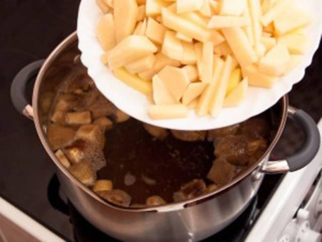 Пока варятся грибы, почистите картофель, порежьте и отправьте в кастрюлю к грибам.