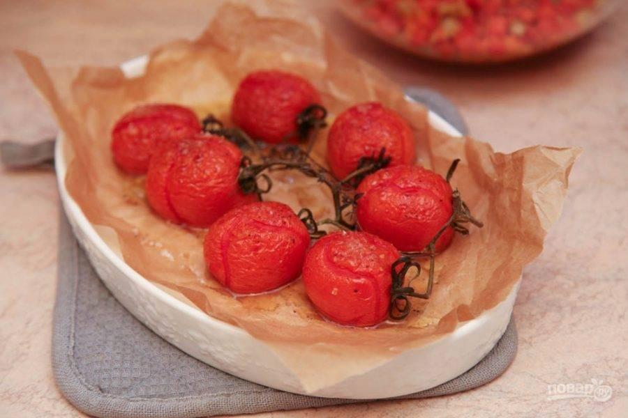 Первым делом необходимо запечь томаты. Для этого вымойте их и выложите на застеленный и смазанный оливковым маслом пергамент, сбрызните маслом сверху, посолите и поперчите.  Запекайте при двухстах градусах в духовке около десяти минут.