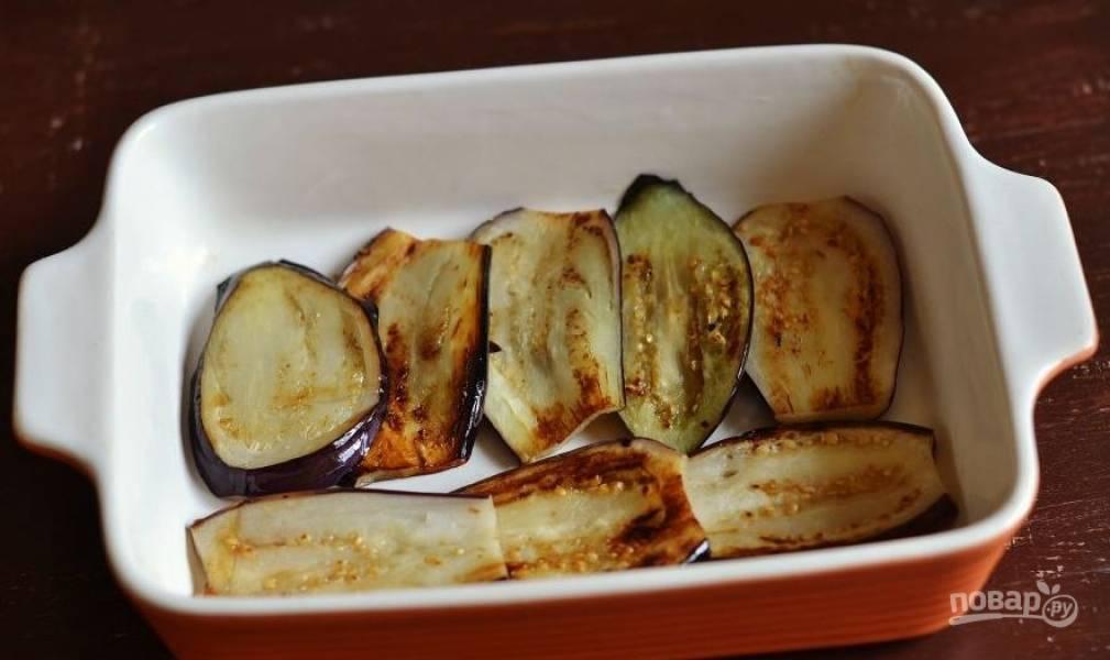 Баклажаны вымойте и нарежьте тонкими пластинами. Обжарьте с обеих сторон на сковороде до мягкости. Выложите баклажаны одним слоем в жаропрочную форму.