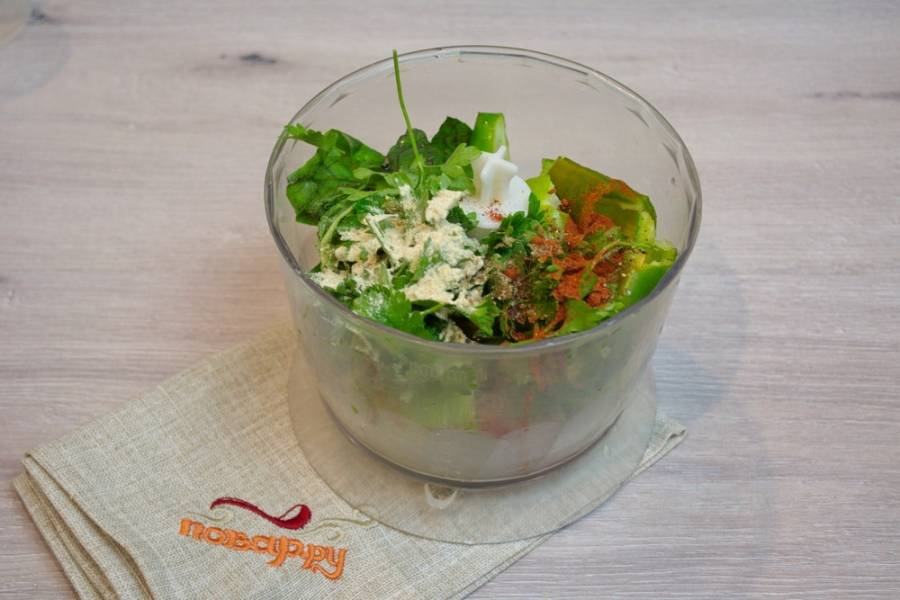 Добавьте в блендер: листики базилика, листики петрушки, кинзы, веточки укропа. Добавьте нарезанный зеленый лук, очищенные зубчики чеснока. Добавьте молотой паприки и  молотого пожитника (чаман).