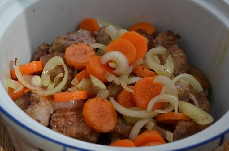 Далее обжариваем на сковороде нарезанную кружочками морковь и лук, нарезанный полукольцами, жарим овощи также до золотистого цвета, затем перекладываем в форму к мясу.