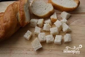 С батона или чиабатты (лучше брать вчерашний подсохший хлеб) срезать корочку, а мякиш нарезать кусочками примерно 1х1 сантиметр.