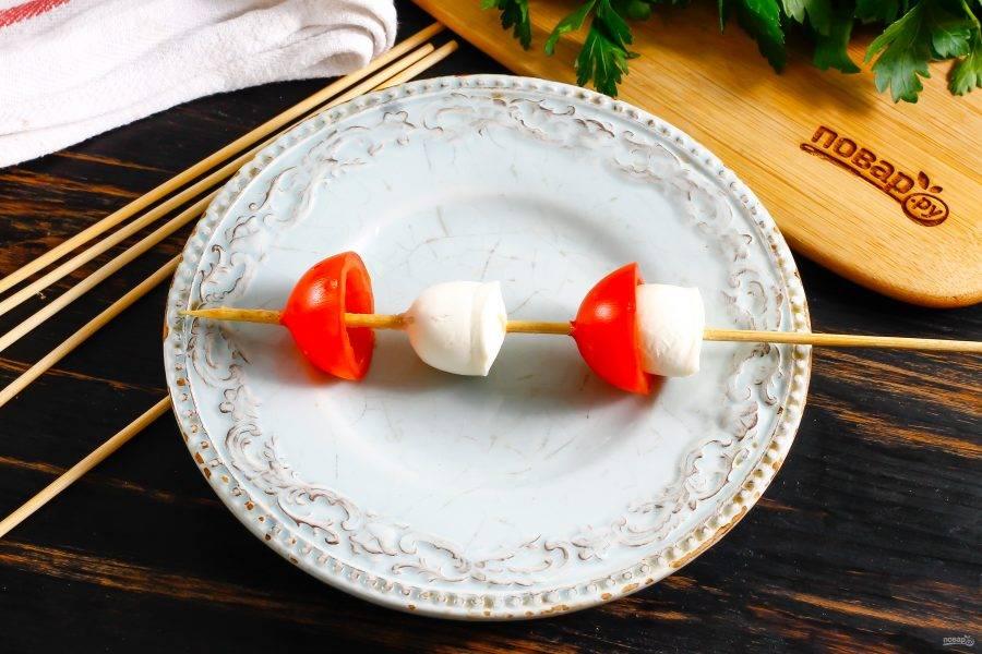 Аккуратно насадите на шпажку сначала орешек моцареллы, широким основанием вниз, затем на него - половинку черри, чтобы получился грибочек. Таким же образом на шпажку насадите еще один грибочек.