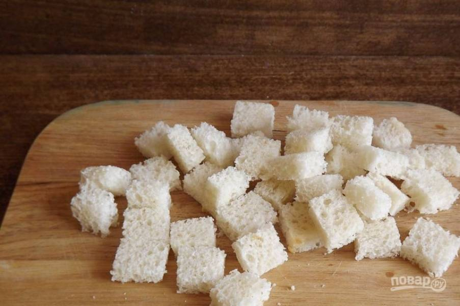 Ломтики белого багета очистите от корок. Затем нарежьте его на небольшие кубики. Поджарьте хлеб на сковороде или запеките в духовке, чтобы он стал золотистого цвета.