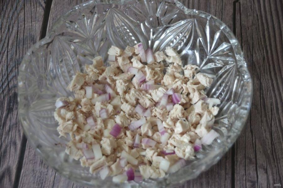 Теперь можно приступить к сборке салата. Первым нижним слоем положите отварную куриную грудку, порезанную кубиком, добавьте лук.