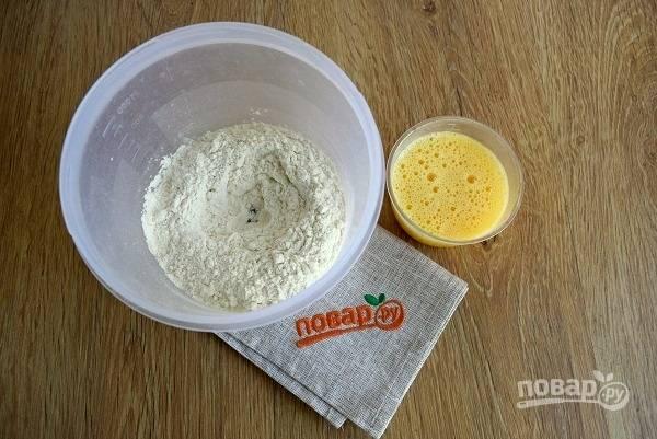 Муку просейте, сделайте по центру углубление. Взбейте яйца с маслом, влейте в муку, перемешайте до однородности.