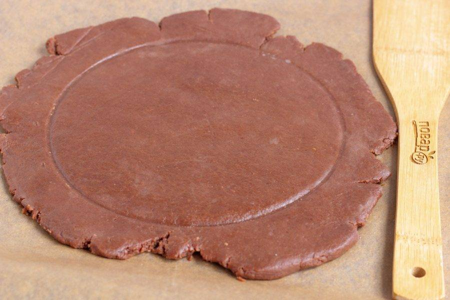 Охлажденное тесто раскатайте в круг, тарелкой пометьте место для начинки, чтобы остались хвостики теста для бортиков.