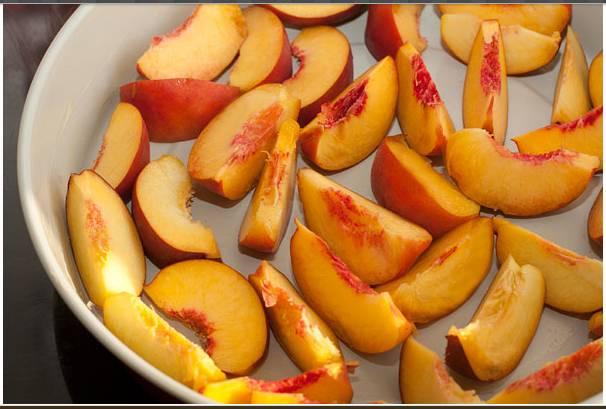 3. Смазываем форму маслом, выкладываем персики, нарезанные тонкими дольками.