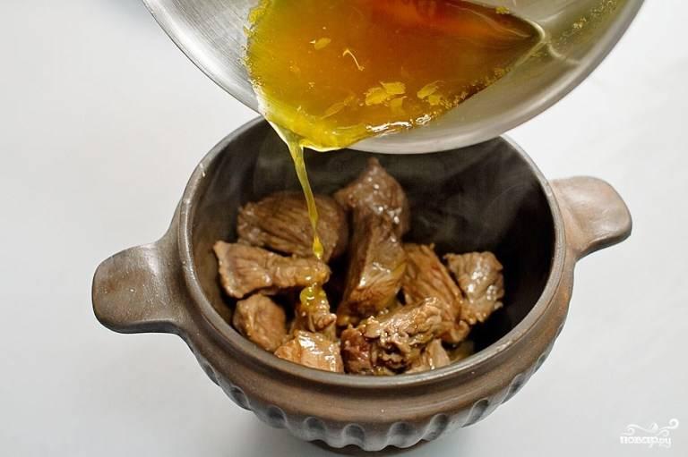 Затем переложите обжаренное мясо в горшочек и залейте апельсиновым сиропом.