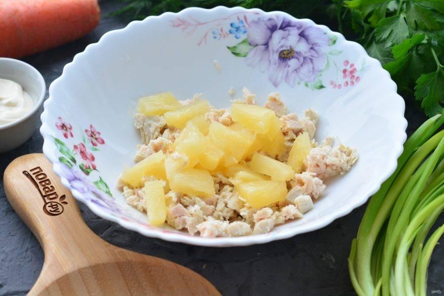 Сложите в емкость куриное филе и добавьте нарезанные ананасы.