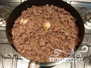 Жарить 2 - 3 минуты, затем добавьте кубик бульона, хорошо перемешать. Добавить 500 г говяжьего фарша, соль и жарить. Когда будет готово, убрать чеснок.