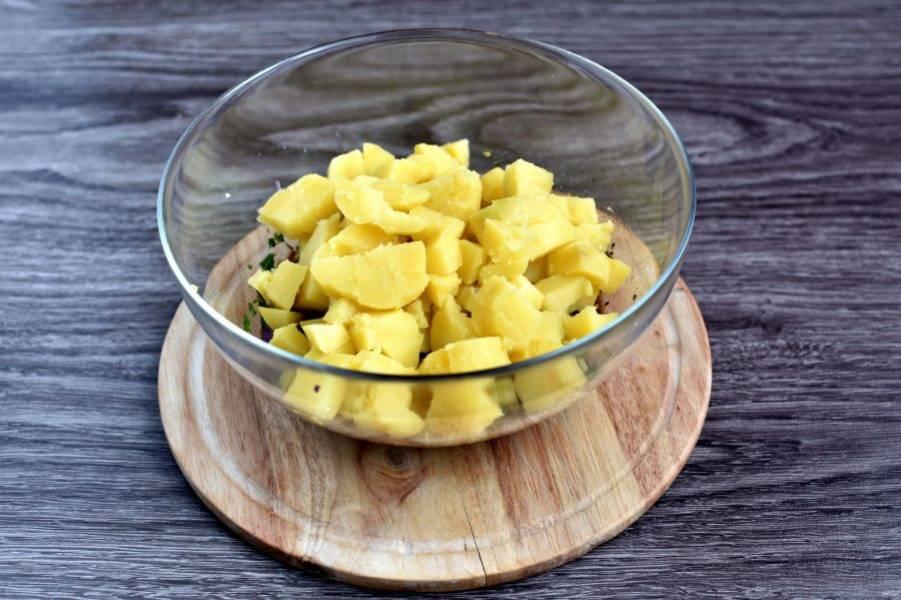 Картофель отварите в мундире и сразу очистите. Порежьте горячий картофель кубиками и выложите в заправку. Перемешайте, дайте остыть и пропитаться заправкой.