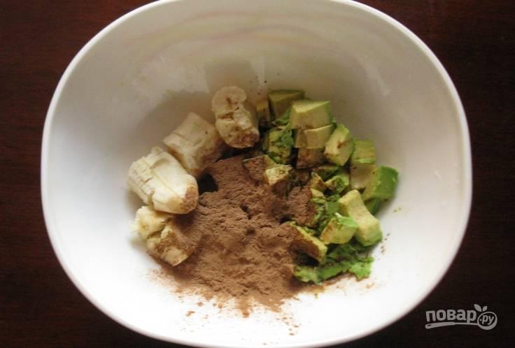 Очищаем авокадо и удаляем косточку. Нарезаем мякоть авокадо и очищенный банан кусочками. Перекладываем овощи в миску, засыпаем кэроб и выдавливаем немного лимонного сока.
