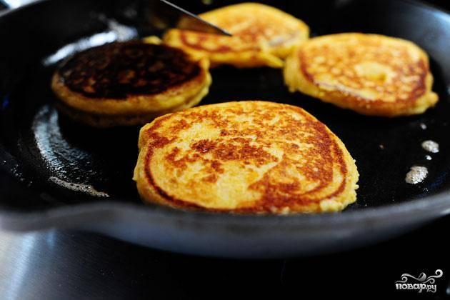 6. Нагреть 1 столовую ложку сливочного масла в сковороде на средне-медленном огне. Вылить тесто в сковороду, используя 1/4 чашки теста на 1 оладью, и готовить до золотистого цвета с обеих сторон. Отложить в сторону готовые оладьи.