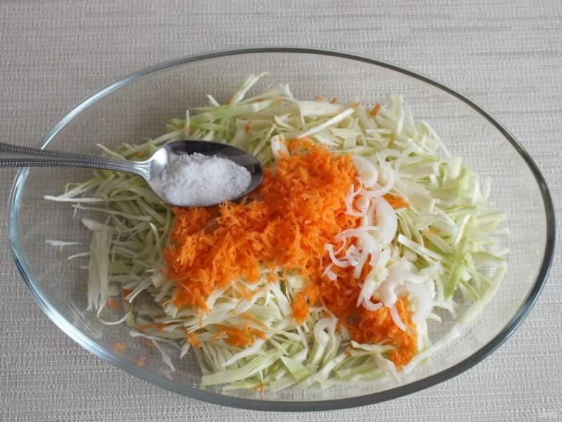 Выложите в чашу нарезанную белокочанную капусту, тертую морковь, нарезанный полукольцами лук, добавьте соль.