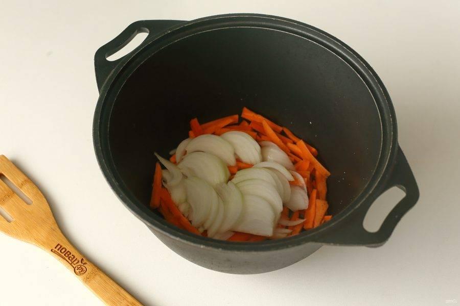 Налейте в казан масло и прогрейте его. Выложите нарезанную соломкой морковь и нарезанный перьями лук.