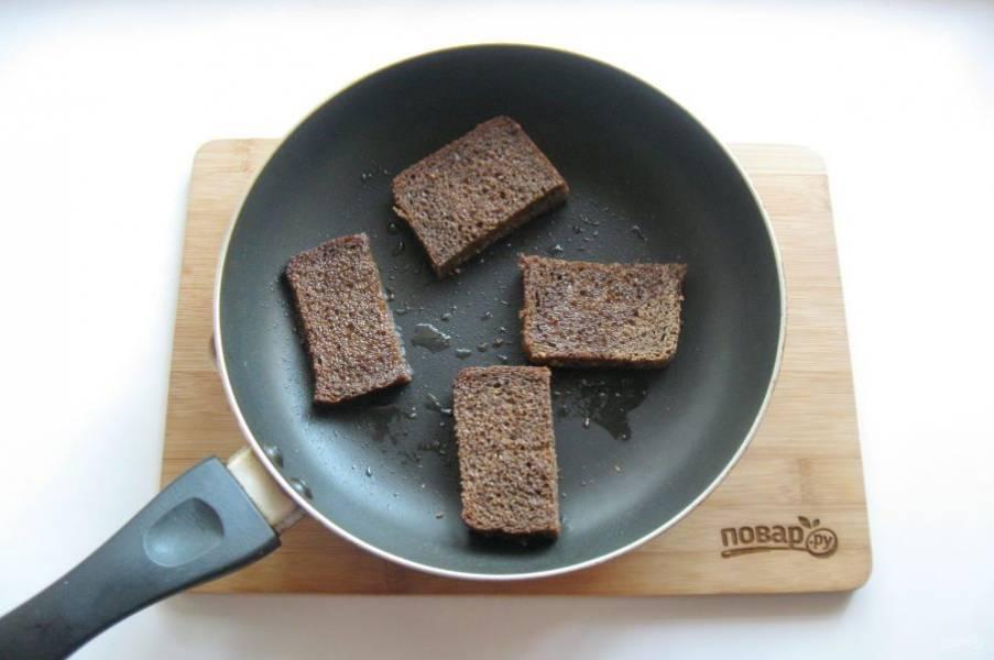Черный хлеб нарежьте ломтиками и поджарьте на сковороде в небольшом количестве подсолнечного масла. Затем натрите чесноком.