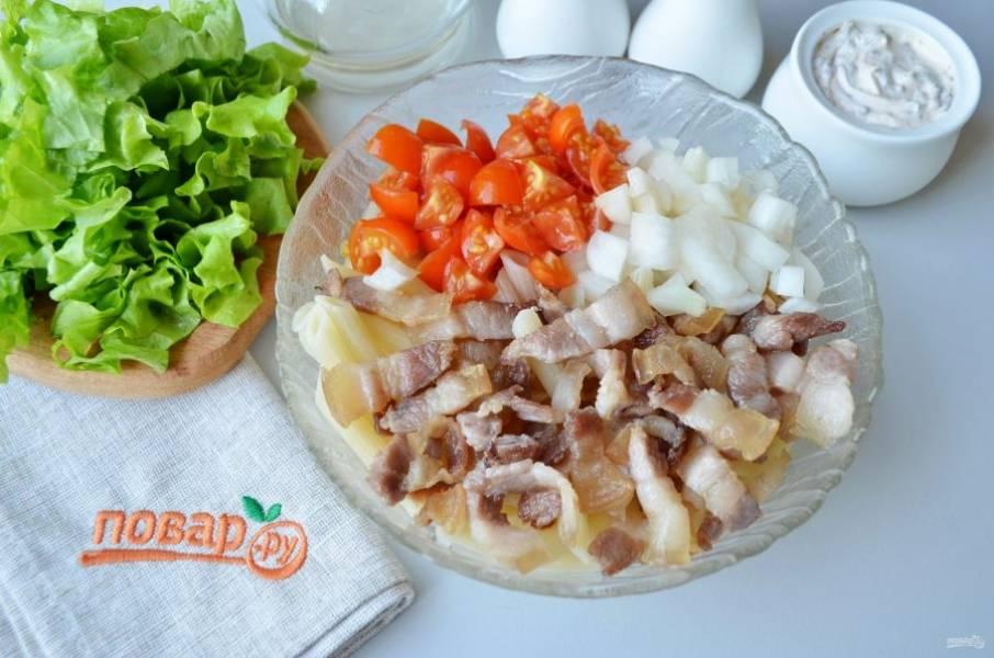К макаронам добавьте бекон, помидоры и лук, перемешайте.
